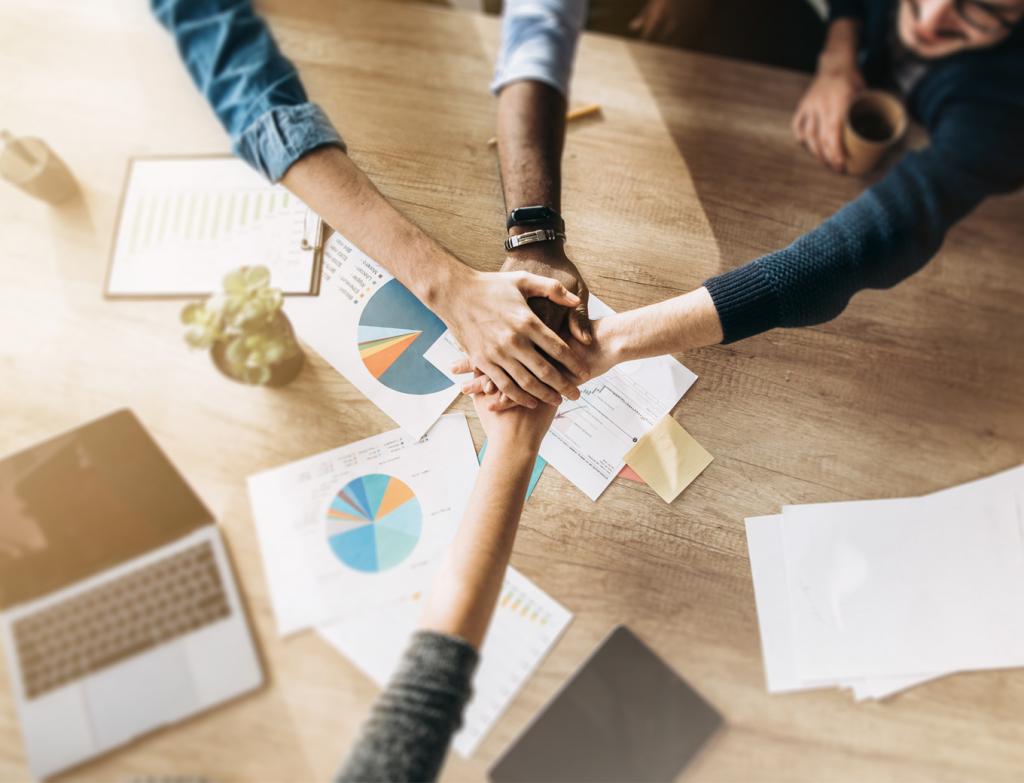 Entrepreneurs hands over table for teamwork